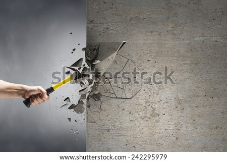 Close up of hammer in hand breaking cement wall - stock photo