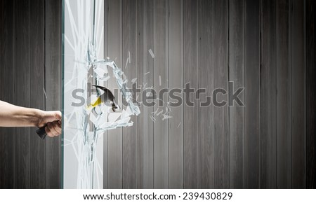 Close up of hammer in human hand breaking glass - stock photo