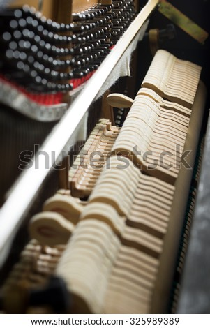 Close up of hammers striking strings inside a piano - stock photo