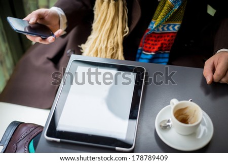 close up of hand and device tablet touching on the table at the bar - stock photo