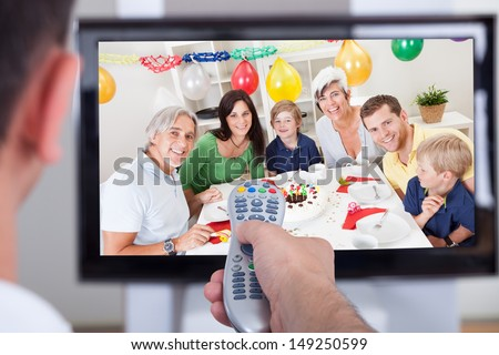 Close up of hand changing television channel through remote - stock photo