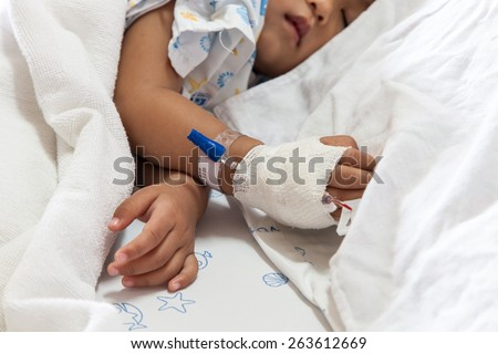 Close up of hand children sick sleeping on the bed at the hospital - stock photo