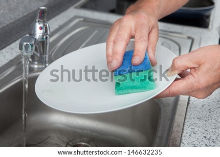 Close-up Of Hand Cleaning Plate With Scrubber - stock photo