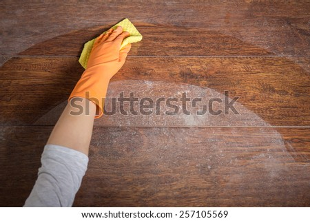 Close-up of hand cleaning wooden table with dishrag - stock photo