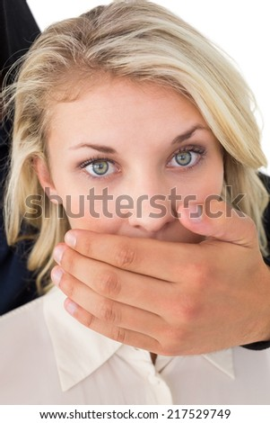 Close up of hand covering young womans mouth over white background - stock photo