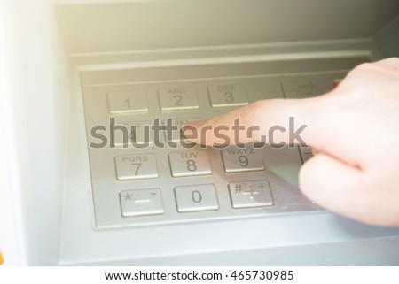 Close up of hand entering pin code at ATM machine to withdraw her money