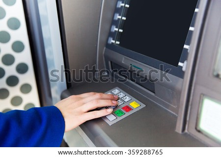 close up of hand entering pin code at cash machine - stock photo