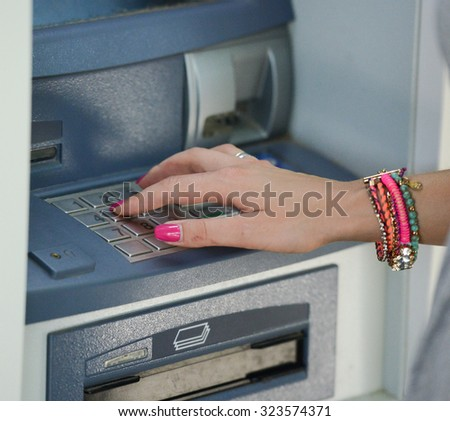 Close-up of hand entering PIN/pass code on ATM/bank machine keypad - stock photo