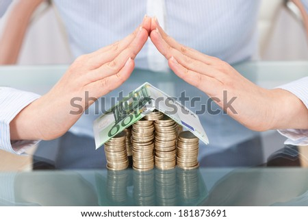 Close-up Of Hand Forming  Roof For House Model Made From Money - stock photo