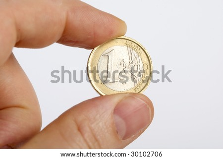 Close-up of hand holding a 1 euro coin