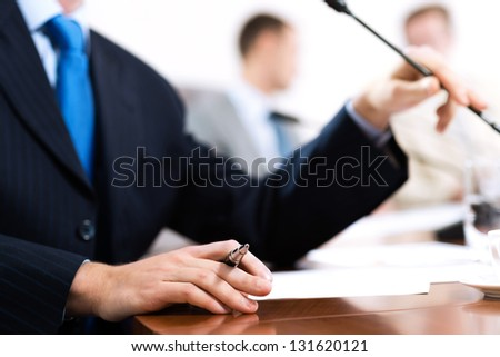 close-up of hand holding a pen, a businessman meeting - stock photo