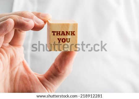 Close Up of Hand Holding Block with Thank You Written on it. - stock photo