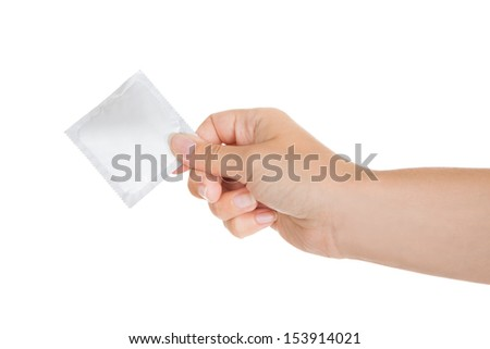 Close-up of hand holding condom packet over white background