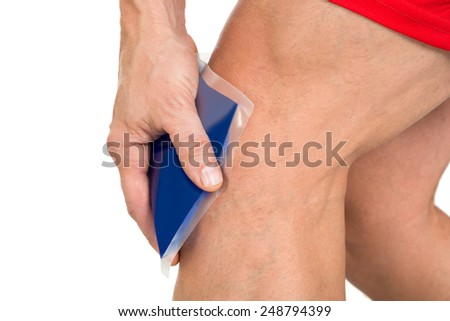 Close-up Of Hand Holding Ice Gel Pack On Painful Knee - stock photo