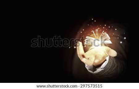 Close up of hand holding in palm glowing book