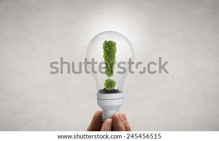 Close up of hand holding light bulb with tree inside - stock photo