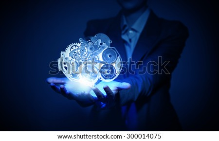 Close up of hand holding media gear icons in palms - stock photo