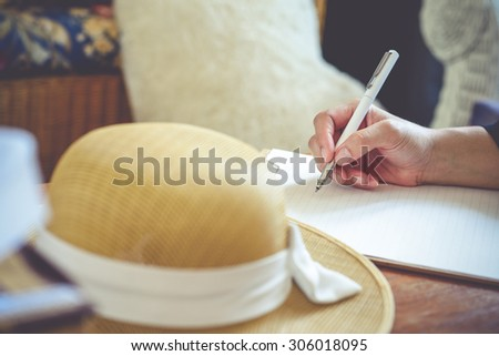 Close-up of hand holding pen and writing in diary of hand writing in diary,Vintage Style - stock photo