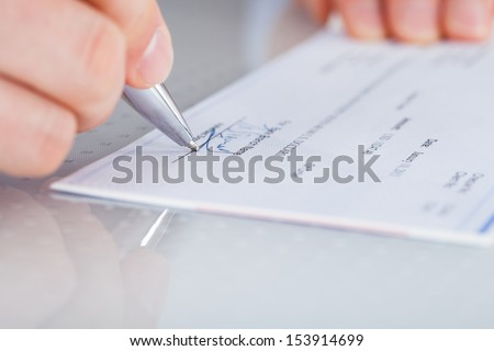 Close-up Of Hand Holding Pen Preparing Writing Check - stock photo