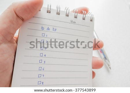 Close-up of  hand holding person's hand writing things To Do List on paper / notepad - stock photo