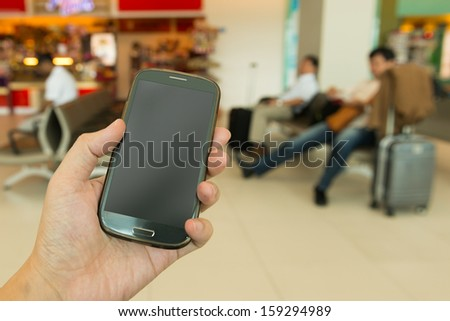 Close up of hand holding smartphone at airport - stock photo