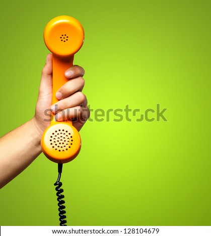 Close Up Of Hand Holding Telephone against a green background - stock photo