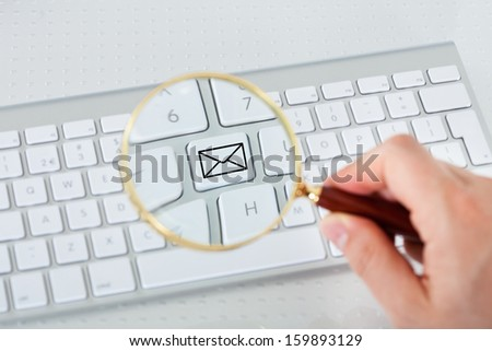 Close-up of hand looking at mail key through magnifying glass - stock photo