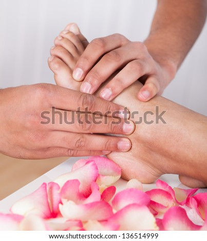 Close-up Of Hand Massaging Foot In Spa - stock photo