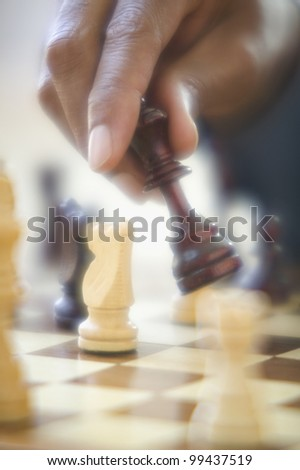 Close up of hand moving chess piece - stock photo
