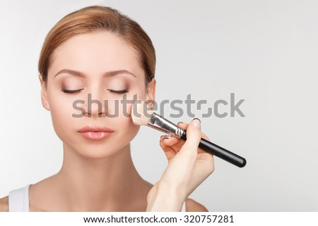 Close up of hand of make-up artist applying powder on female face. The woman is holding a brush. The model closed her eyes with relaxation. Isolated and copy space in right side - stock photo