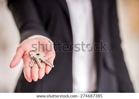 Close-up of hand of realtor woman is holding key. - stock photo
