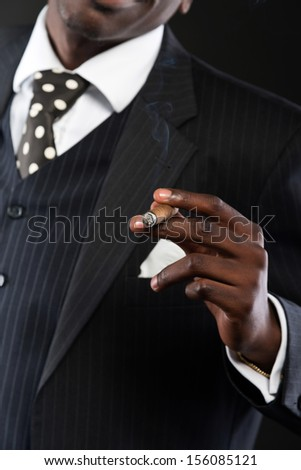 Close-up of hand of retro african american mafia man wearing striped suit and tie. Smoking cigar. Studio shot.