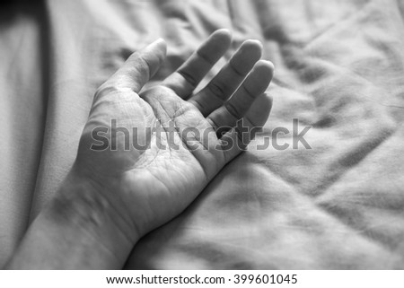 Close-up of  hand on the bed black and white