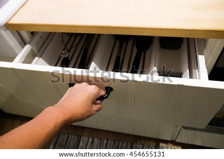 Close up of hand opening a white drawer in the kitchen