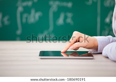 Close-up Of Hand Over Digital Tablet Screen In Front Of Chalkboard - stock photo