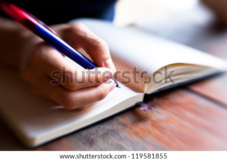 Close-up of hand pen writes in a notebook (blurred) - stock photo