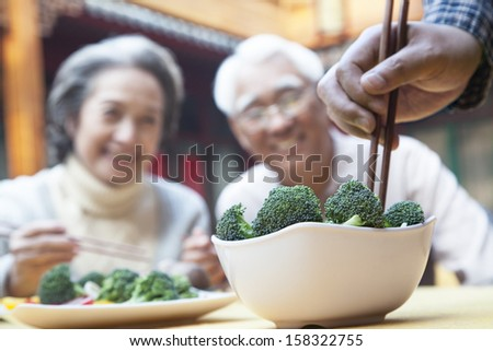 Close up of hand picking up broccoli with chopsticks - stock photo
