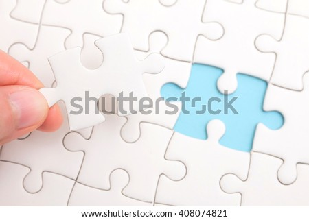 Close up of hand placing the last jigsaw puzzle piece conceptual of problem solving, finding a solution. - stock photo