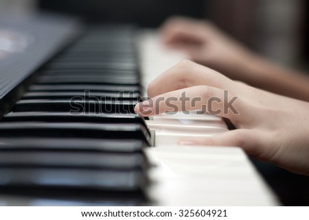 Close-up of hand playing the piano