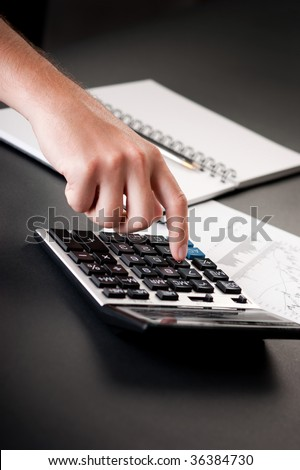 Close-up of hand pressing button on calculator with stock charts and notepad - stock photo