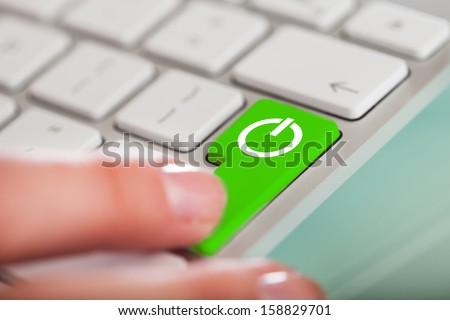 Close-up Of Hand Pushing The Power Button On Keyboard - stock photo