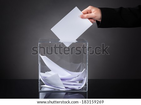 Close-up Of Hand Putting Ballot In Glass Box - stock photo