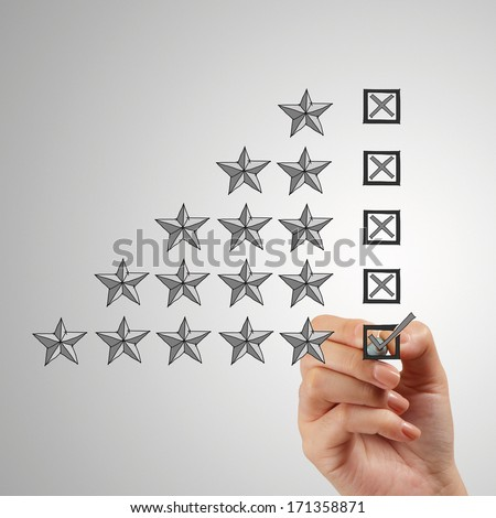 close up of hand putting check mark  on five star rating on screen as concept