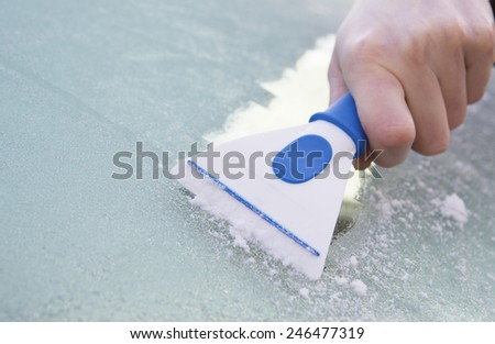 Close Up Of Hand Scraping Ice From Car Windshield With Scraper - stock photo
