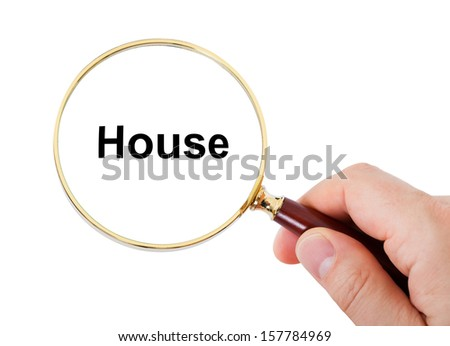Close-up Of Hand Showing House Word Through Magnifying Glass Over White Background
