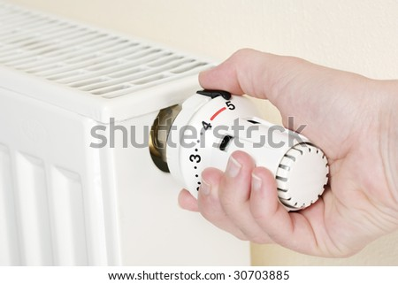 Close-up of hand turning thermostat to full heating position - stock photo
