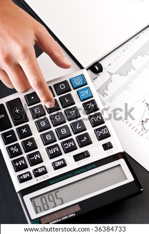 Close-up of hand using calculator with stock charts and notepad - stock photo