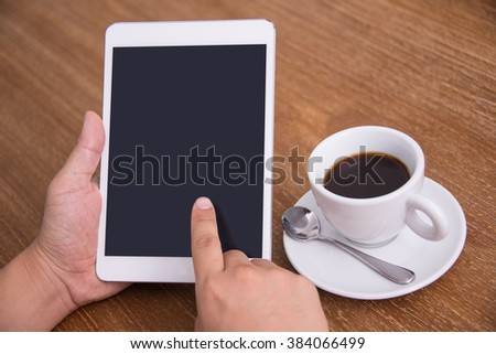 Close-up of hand using digital tablet with black coffee at desk.