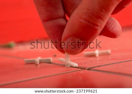 Close Up of Hand Using Tile Spacers in Preparation for Grouting on Red Tiles. - stock photo