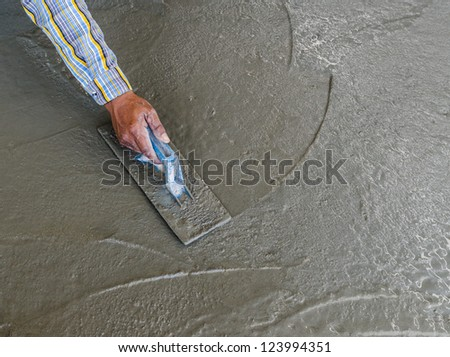 Close-up of hand using trowel to finish wet concrete floor - stock photo